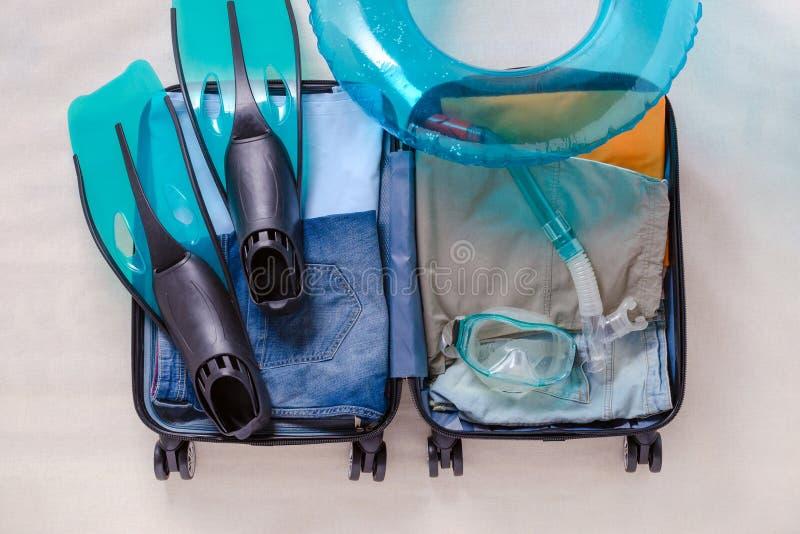 Η ανοικτή βαλίτσα ταξιδιού με τα ενδύματα και τα βατραχοπέδιλα και κολυμπούν με αναπνευτήρα μάσκα, τοπ άποψη στοκ φωτογραφία