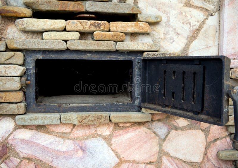 Η ανοικτή σφυρηλατημένη πόρτα φύσηξε έναν μεγάλο φούρνο στοκ εικόνες