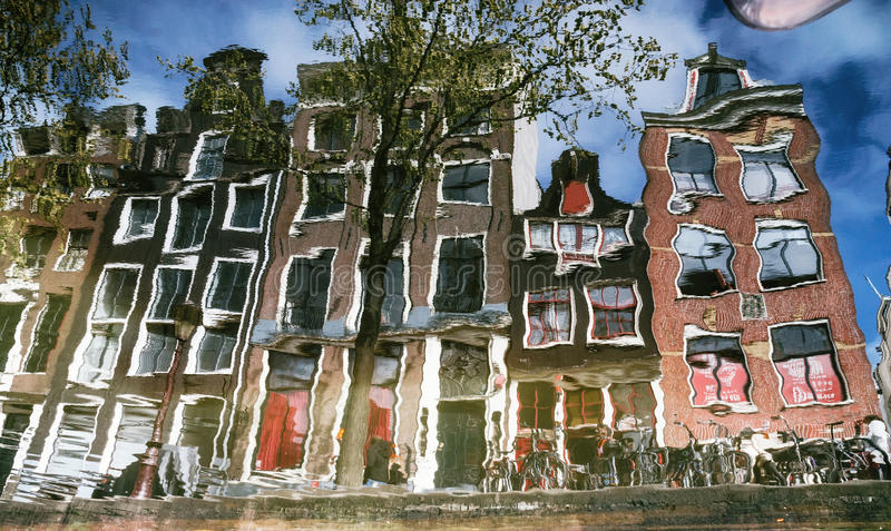 Η αντανάκλαση των χαρακτηριστικών στενών σπιτιών με τα μεγάλα παράθυρα στο κανάλι, Άμστερνταμ στοκ εικόνα