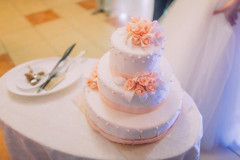 Η ανωτέρω άποψη κινηματογραφήσεων σε πρώτο πλάνο του άσπρου γαμήλιου κέικ που διακοσμείται με τα τριαντάφυλλα στοκ φωτογραφίες