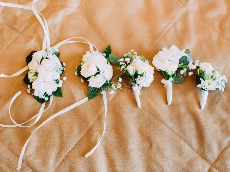 Η ανωτέρω άποψη των γαμήλιων μίνι-ανθοδεσμών και armlet λουλουδιών που τυλίγονται στις άσπρες κορδέλλες που τοποθετούνται στο κρε στοκ φωτογραφίες με δικαίωμα ελεύθερης χρήσης