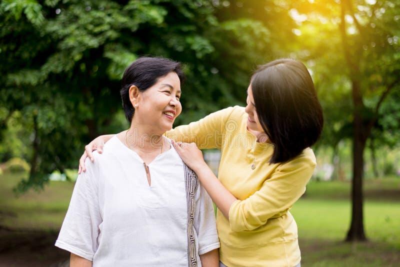 Η ανώτερη ασιατική παλαιότερη μητέρα ευχαριστημένη από την κόρη χεριών παίρνει την προσοχή και η υποστήριξη, κλείνει επάνω στοκ φωτογραφίες