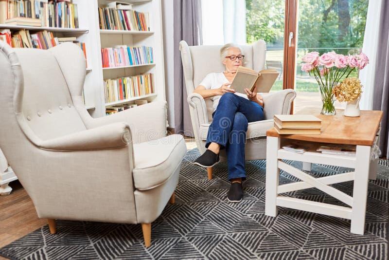 Η ανώτερη γυναίκα διαβάζει συγκεντρωμένος σε ένα βιβλίο στοκ εικόνες