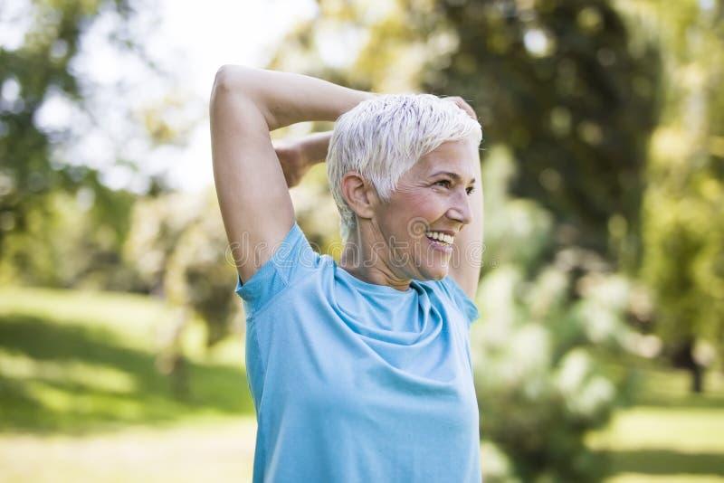 Η ανώτερη γυναίκα που κάνει την άσκηση για το τέντωμα παραδίδει το πάρκο στοκ φωτογραφίες με δικαίωμα ελεύθερης χρήσης