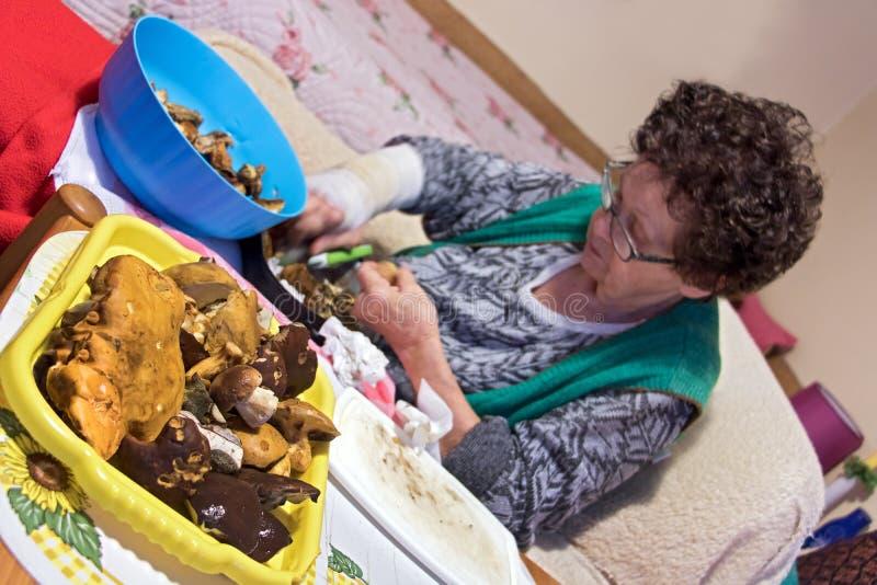 Η ανώτερη γυναίκα προετοιμάζει τα μαγειρεύοντας μανιτάρια στοκ εικόνες