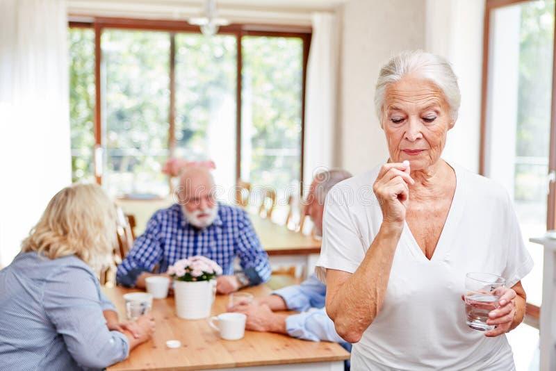 Η ανώτερη γυναίκα στο σπίτι των ηλικιωμένων παίρνει μια ταμπλέτα στοκ φωτογραφίες