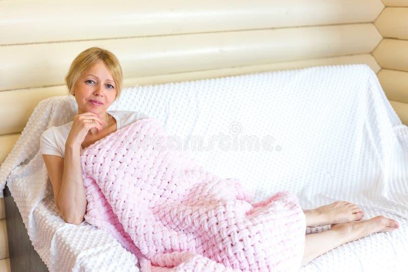 Η ανώτερη γυναίκα χαλαρώνει κάτω από ένα θερμό κάλυμμα στοκ εικόνες με δικαίωμα ελεύθερης χρήσης