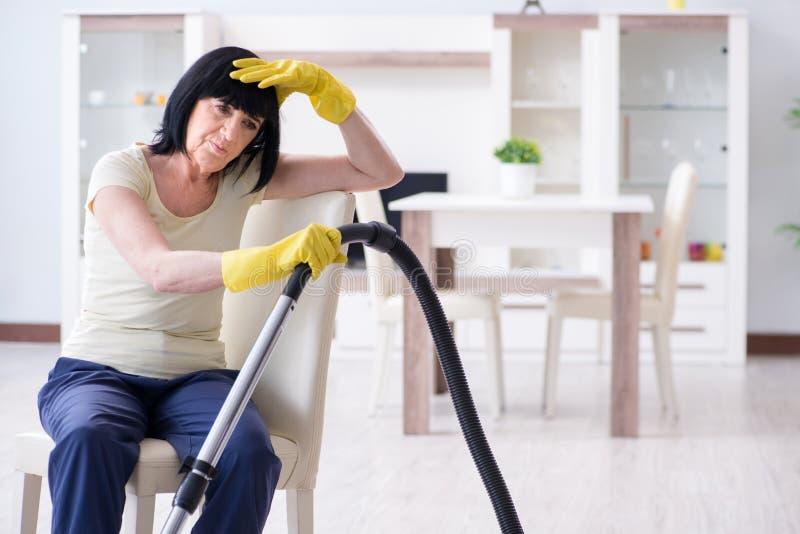 Η ανώτερη ηλικιωμένη γυναίκα κούρασε μετά από το κενό καθαρίζοντας σπίτι στοκ εικόνες με δικαίωμα ελεύθερης χρήσης