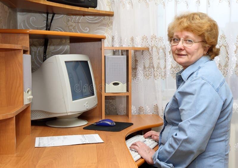 Η ανώτερη κυρία μαθαίνει έναν υπολογιστή. στοκ εικόνες