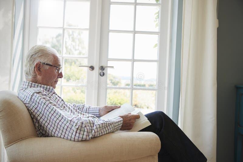 Η ανώτερη συνεδρίαση ατόμων σε μια πολυθρόνα που διαβάζει ένα βιβλίο, κλείνει επάνω στοκ εικόνες