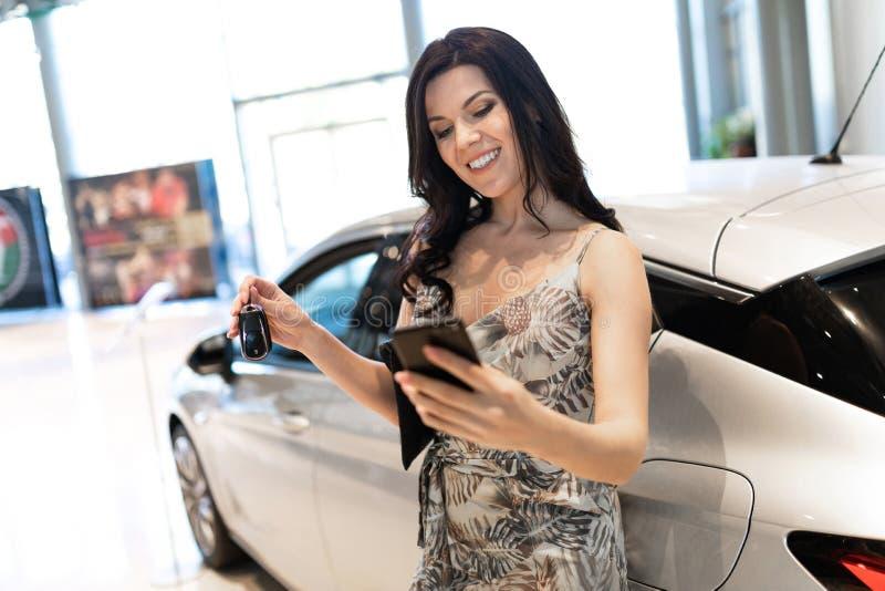 Η αξιοθαύμαστη brunet ομιλία τηλεφωνούν και κοντά στο νέο αυτοκίνητό της στην αίθουσα εκθέσεως αντιπροσώπων στοκ εικόνα