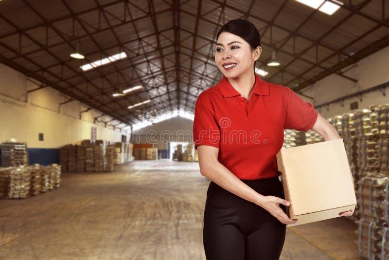 Η αρκετά ασιατική γυναίκα αγγελιαφόρων φέρνει τη συσκευασία στοκ εικόνα