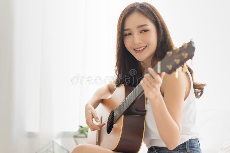 Η αρκετά ασιατική γυναίκα ασκεί την κιθάρα στοκ εικόνες με δικαίωμα ελεύθερης χρήσης