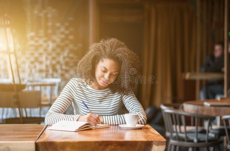 Η αρκετά αφρικανική γυναίκα μαθαίνει υπαγόμενο στην καφετέρια στοκ εικόνες με δικαίωμα ελεύθερης χρήσης