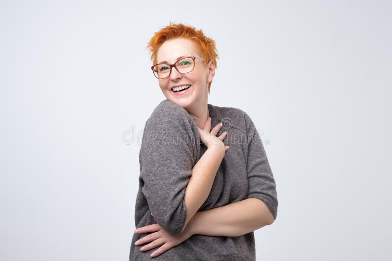Η αρκετά καυκάσια ώριμη γυναίκα με το σύντομο κόκκινο hairstyle στο απλό pulover είναι ντροπαλή για να ακούσει μια φιλοφρόνηση στοκ φωτογραφία