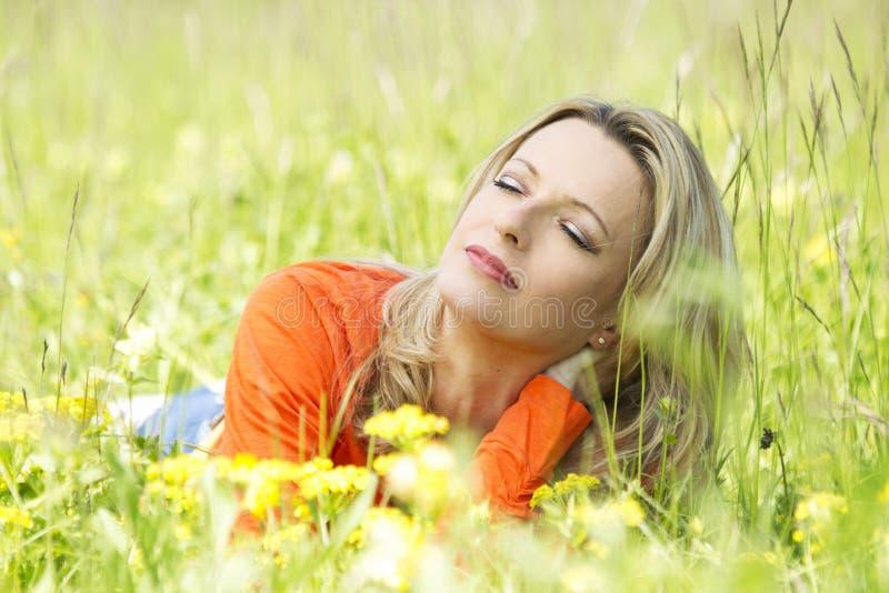 Η αρκετά μέση ηλικίας γυναίκα χαλαρώνει στοκ εικόνες