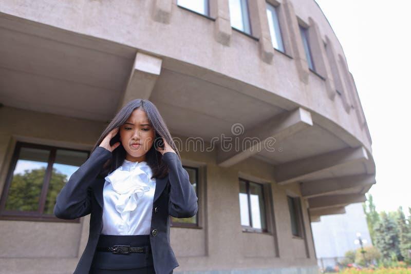 Η αρκετά νέα ασιατική επιχειρησιακή γυναίκα, σπουδαστής κρατά στο κεφάλι από το FA στοκ εικόνα