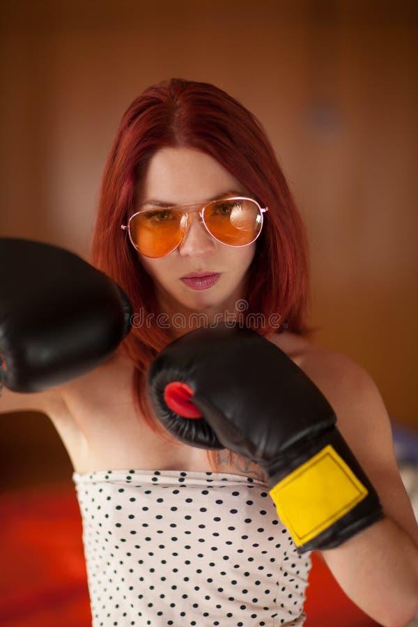 Η αρκετά νέα γυναίκα με την κόκκινη τρίχα, τα γυαλιά ηλίου και τα εγκιβωτίζοντας γάντια φαίνεται στοκ φωτογραφία με δικαίωμα ελεύθερης χρήσης