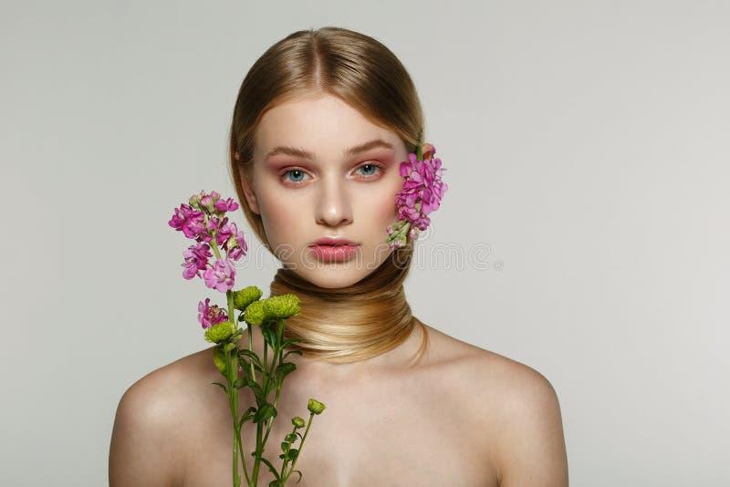 Η αρκετά νέα γυναίκα με το φρέσκο ελατήριο κοιτάζει, θαυμάσια τρίχα, συμπαθητικό makeup, λουλούδια κοντά στο πρόσωπό της και στην στοκ φωτογραφία