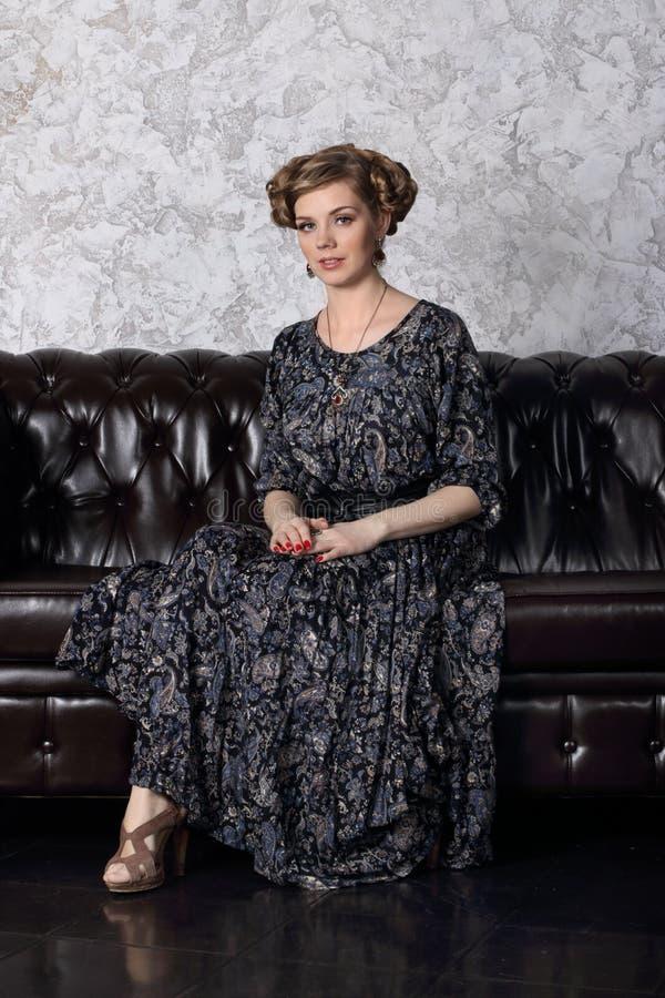Η αρκετά νέα γυναίκα με το hairdo και στο φόρεμα κάθεται στον καναπέ στοκ φωτογραφία