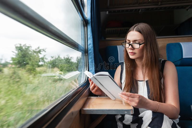 Η αρκετά νέα γυναίκα σε ένα μοντέρνο ριγωτό θερινό φόρεμα στα γυαλιά κάθεται στο τραίνο κοντά στο παράθυρο και διαβάζει ένα ενδια στοκ φωτογραφίες