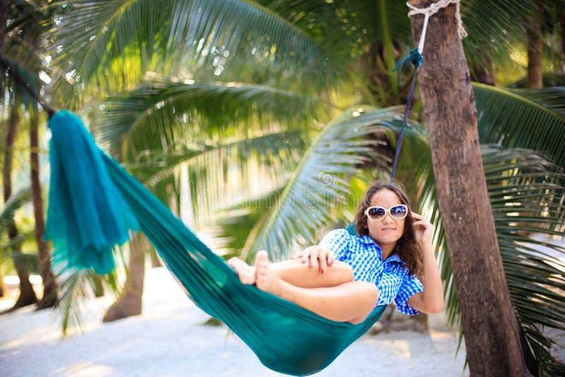 Η αρκετά νέα γυναίκα στα γυαλιά ηλίου στηρίζεται στην αιώρα κάτω από τους φοίνικες στην τροπική παραλία στοκ φωτογραφία με δικαίωμα ελεύθερης χρήσης