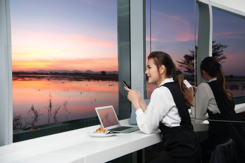 Η αρκετά νέα επιχειρησιακή ασιατική γυναίκα απασχολείται σε μια συνεδρίαση lap-top σε ένα κτήριο στοκ εικόνες με δικαίωμα ελεύθερης χρήσης