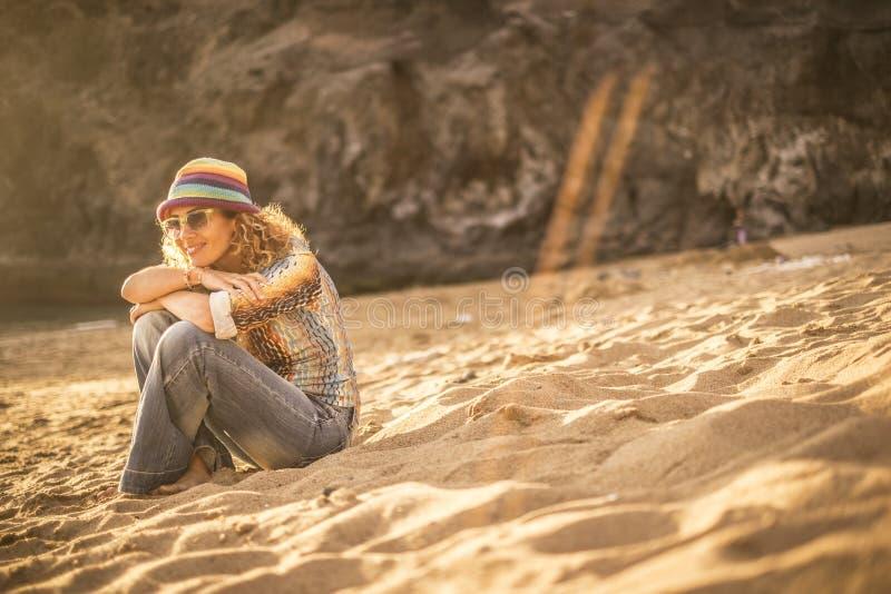 Η αρκετά ξανθή νέα γυναίκα κάθεται στην άμμο στην παραλία που χαλαρώνει και που απολαμβάνει το ηλιοβασίλεμα και την ηλιόλουστη ημ στοκ φωτογραφίες