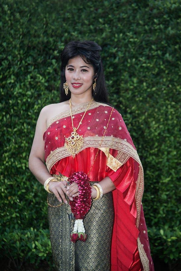 Η αρκετά ταϊλανδική κυρία στη μέση ταϊλανδική κλασσική παραδοσιακή γιρλάντα στάσης και λαβής κοστουμιών φορεμάτων θέτει σε ένα πά στοκ φωτογραφία με δικαίωμα ελεύθερης χρήσης