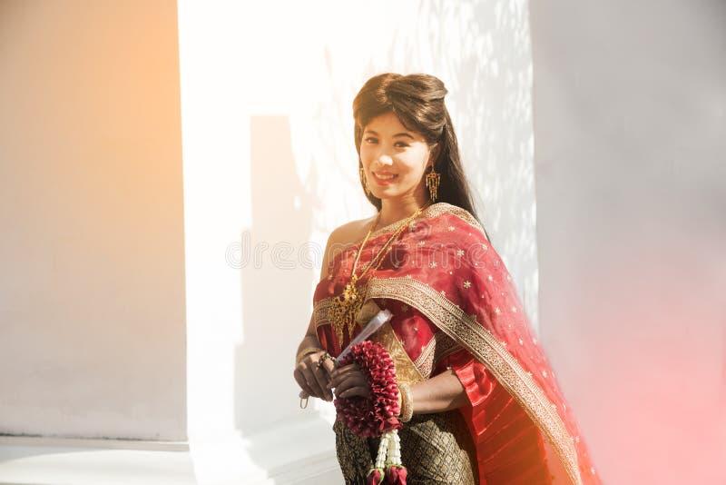 Η αρκετά ταϊλανδική κυρία στη μέση ταϊλανδική κλασσική παραδοσιακή γιρλάντα στάσης και λαβής κοστουμιών φορεμάτων θέτει στο άσπρο στοκ εικόνες
