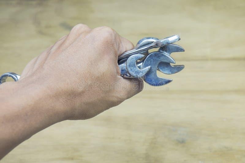 Η αρπαγή χεριών, κρατά τα παλαιά, σκουριασμένα εργαλεία σε έναν ξύλινο πίνακα στοκ φωτογραφία