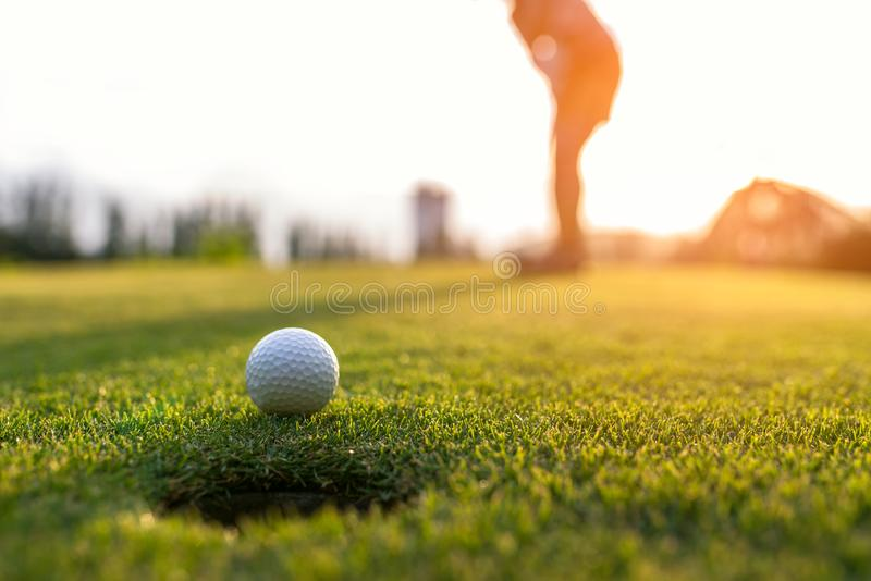 Η ασιατική γυναίκα παικτών γκολφ που βάζει τη σφαίρα γκολφ στο πράσινο γκολφ στον καθορισμένο χρόνο βραδιού ήλιων, επιλέγει την ε στοκ φωτογραφίες με δικαίωμα ελεύθερης χρήσης