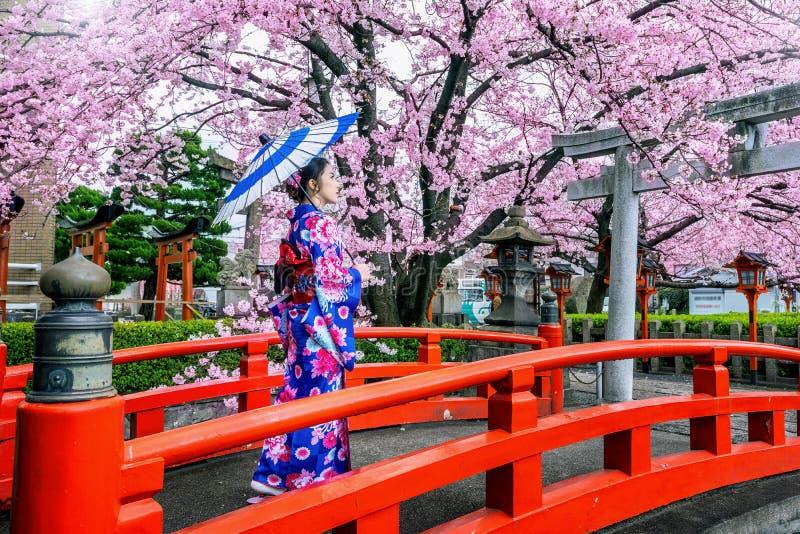 Η ασιατική γυναίκα που φορούν το ιαπωνικό παραδοσιακό κιμονό και το κεράσι ανθίζουν την άνοιξη, ναός του Κιότο σε Japanใ στοκ εικόνες