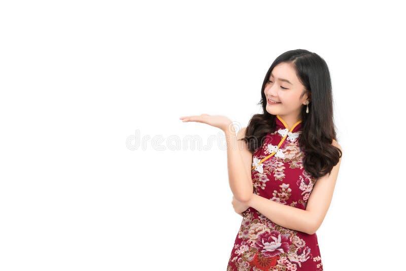 Η ασιατική γυναίκα που φορούν το κινεζικό φόρεμα, cheongsam, το παρόν qipao και παρουσιάζουν κάτι στο διάστημα αντιγράφων στοκ εικόνες
