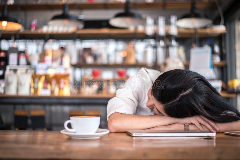 Η ασιατική γυναίκα στηρίζεται και κοιμάται σε μια καφετερία επειδή είναι κουρασμένη να εργαστεί όλη τη νύχτα Ιδιοκτήτης επιχείρησ στοκ εικόνα