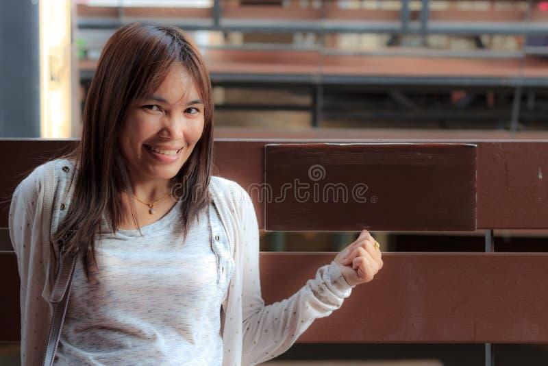 Η ασιατική γυναίκα χαμόγελου κάθεται στην έδρα. στοκ εικόνες με δικαίωμα ελεύθερης χρήσης