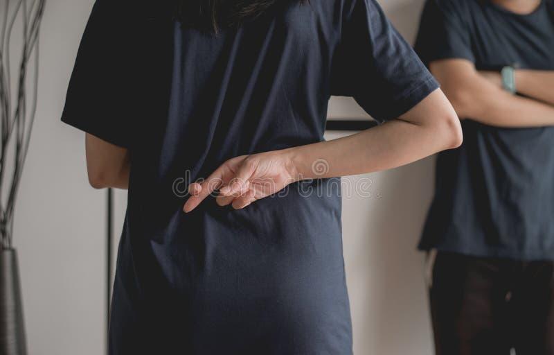 Η ασιατική γυναίκα ψευτών με το χέρι που διασχίζει τα δάχτυλα πίσω από την πίσω αφήγηση βρίσκεται και την εξαπάτηση στο φίλο, ένν στοκ εικόνες