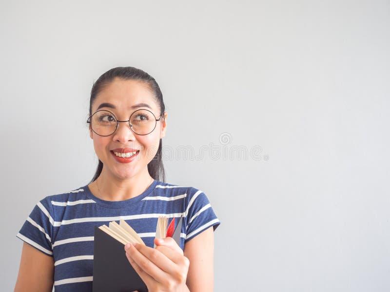 Η ασιατική γυναίκα Nerd πήρε μια έκπληκτη ιδέα από το βιβλίο στοκ εικόνες