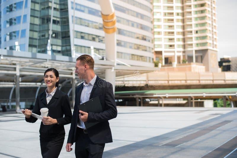 Η ασιατική επιχειρησιακή γυναίκα και ο καυκάσιος επιχειρηματίας φορούν το κοστούμι περπατώντας στην πόλη και τη συζήτηση για το ε στοκ φωτογραφία με δικαίωμα ελεύθερης χρήσης