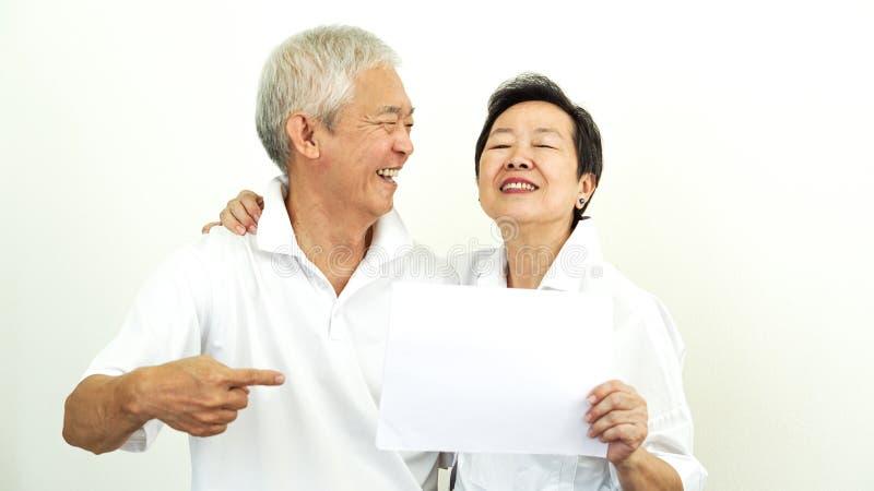 Η ασιατική ηλικιωμένη ζευγών διαφήμιση σημαδιών λαβής κενή ευτυχής συστήνει στοκ εικόνα