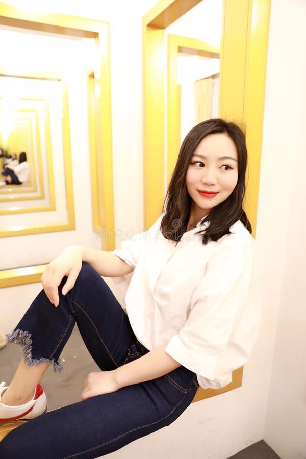 Η ασιατική κινεζική γυναίκα στο δωμάτιο συναρμολογήσεων εξετάζει την από τον καθρέφτη συναρμολογήσεων στοκ εικόνες με δικαίωμα ελεύθερης χρήσης