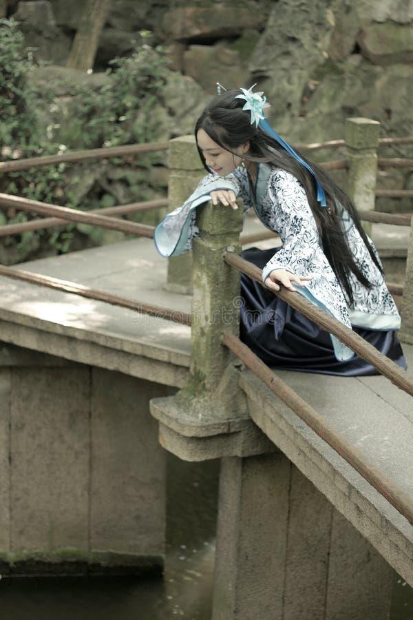 Η ασιατική κινεζική γυναίκα στο παραδοσιακό μπλε και άσπρο φόρεμα Hanfu, παιχνίδι σε έναν διάσημο κήπο αναρριχείται στην καμμμένη στοκ φωτογραφία με δικαίωμα ελεύθερης χρήσης