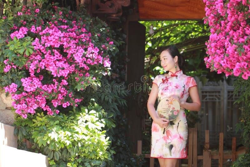 Η ασιατική κινεζική γυναίκα στο παραδοσιακό cheongsam απολαμβάνει το ελεύθερο χρόνο στο lijiang στοκ εικόνες