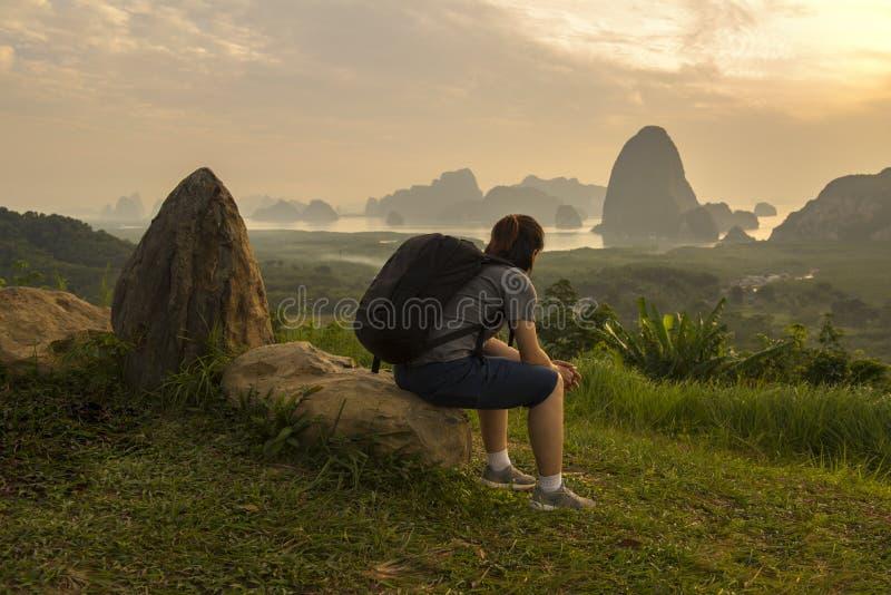 Η ασιατική κυρία με τη μαύρη τσάντα κάθεται στο βράχο εξετάζει την άποψη βουνών και ποταμών στοκ εικόνες