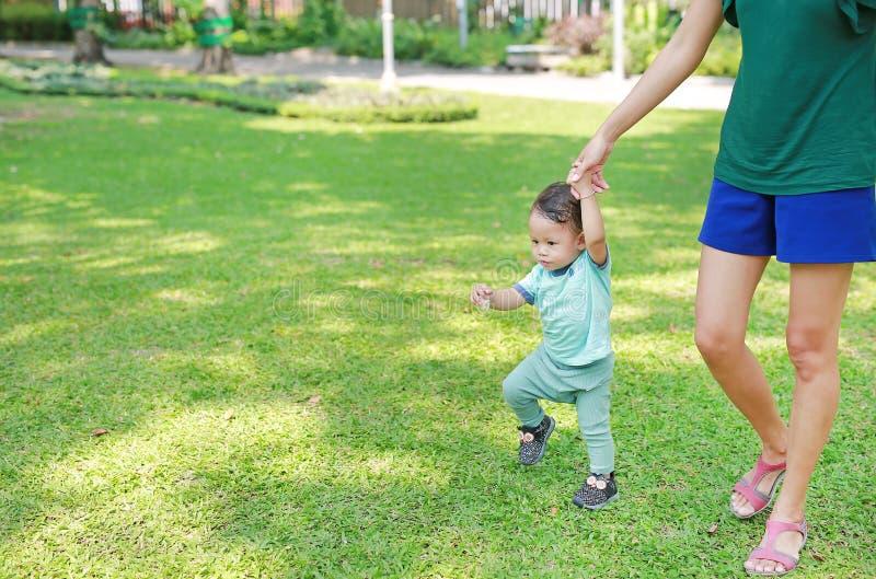 Η ασιατική μητέρα που μαθαίνει το μωρό νηπίων της για να περπατήσει τα πρώτα βήματα στην πράσινη χλόη καλλιεργεί στοκ εικόνες
