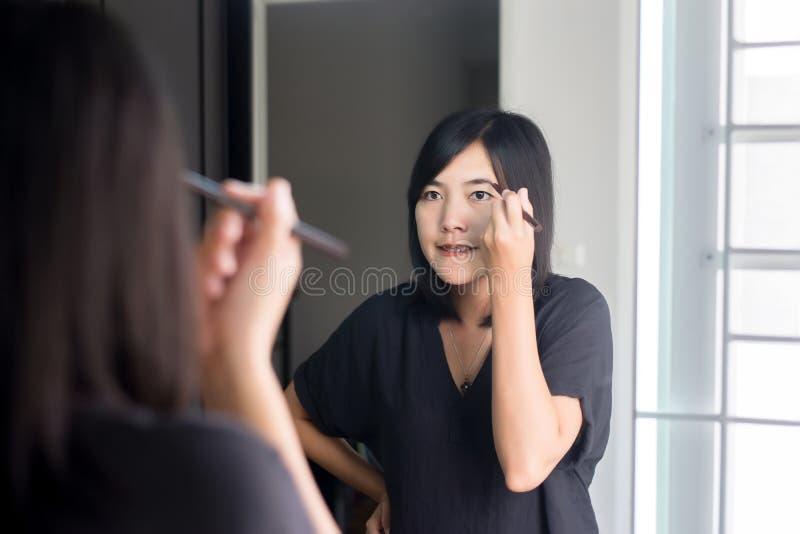 Η ασιατική μορφή φρυδιών διόρθωσης γυναικών με τη βούρτσα, Makeup και η όμορφη γυναίκα αντιμετωπίζουν στοκ εικόνες