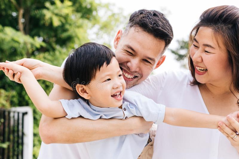 Η ασιατική οικογένεια που έχει τη διασκέδαση και που φέρνει ένα παιδί σταθμεύει δημόσια στοκ φωτογραφίες