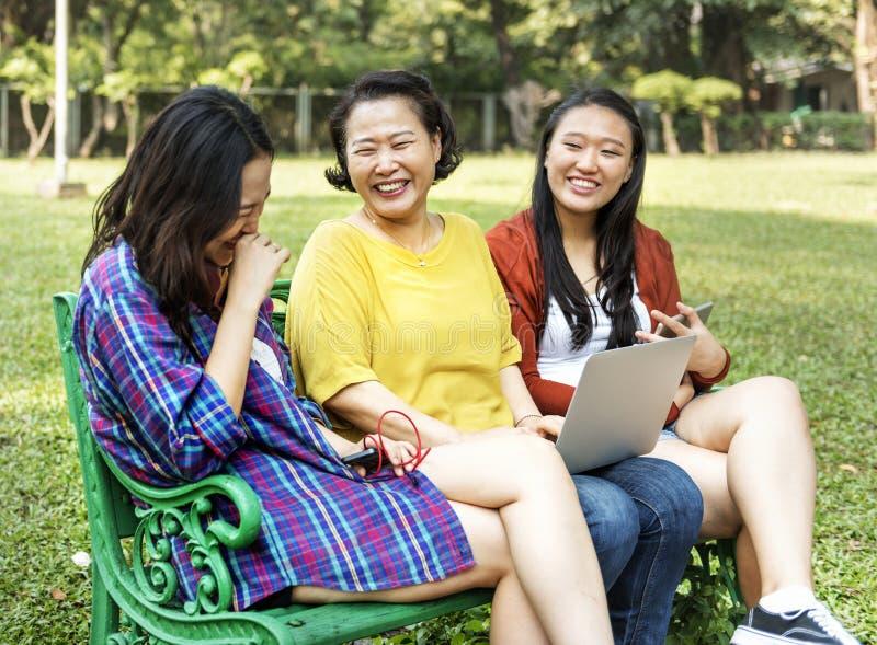 Η ασιατική οικογένεια χρησιμοποιεί τις ψηφιακές συσκευές στο πάρκο στοκ φωτογραφίες