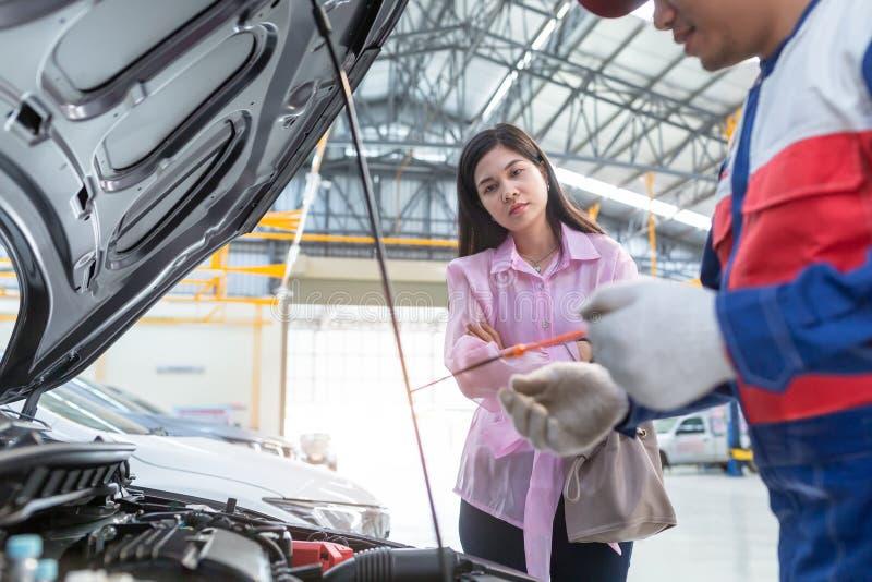Η ασιατική ομιλία γυναικών μηχανικών και πελατών αυτοκινήτων σε έναν μηχανικό αυτοκινήτων στο κέντρο υπηρεσιών αυτοκινήτων, και τ στοκ φωτογραφία