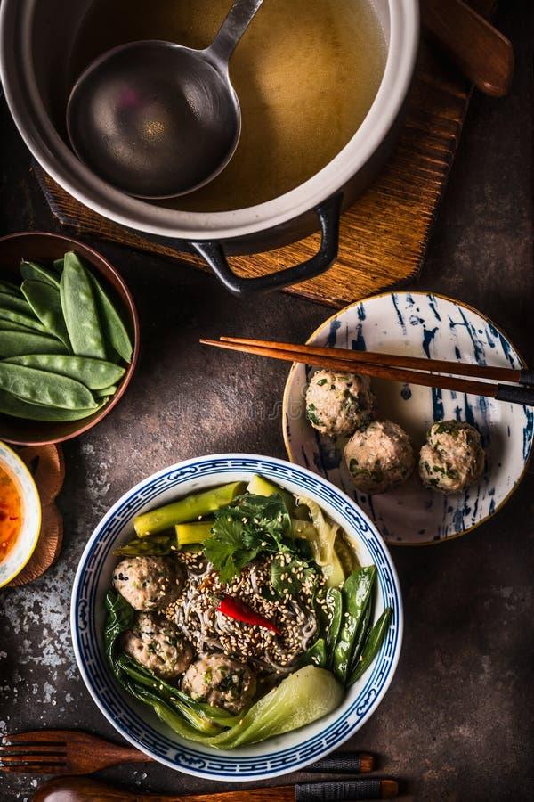 Η ασιατική σούπα νουντλς κεφτών στο κύπελλο με chopsticks εξυπηρέτησε στο σκοτεινό αγροτικό υπόβαθρο, τοπ άποψη Ασιατική έννοια κ στοκ εικόνες